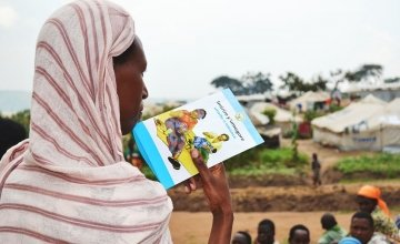 Denise holding a BCC material on nutrition for pregnant and lactating women. Photo taken by Donna Ajamboakaliza / Concern Worldwide.