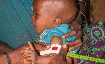 Emeline Niyonkuru a community health worker screening 6 month old Ghislaine who is severely malnourished in Cibitoke. Photo: Irenee Nduwayezu/Concern Worldwide.