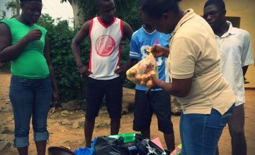 Concern quarantine worker Ruth present relief goods to a community leader in Liberia. Photo taken by Concern Worldwide