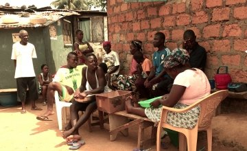 A quarantined family sit in the shade of their home in Liberia. Photo taken by Concern Worldwide.