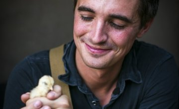 TV host and cook, Donal Skehan, with a Malawian chick in Jambawe village, Malawi. Chicks like this can be donated to Malawian communities through Concern Christmas Gifts. Photo: Jennifer Nolan/Concern Worldwide.