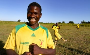 Mwale Chibiliro (18) in sports kit and football boots from Concern Worldwide.
