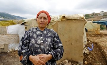 A 55-year old Syrian refugee stands in front of her makeshift shelter in an informal tented settlement near the Syrian border in north Lebanon, February 2015. Photo taken by Dalia Khamissy / Concern Worldwide.