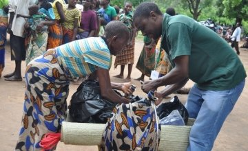 Johannes Chikarate helps a women who has been displaced due to the floods in Malawi to pack up the items she has received from Concern in Nsanje District. Credit: Deborah Underdown / Concern Worldwide.