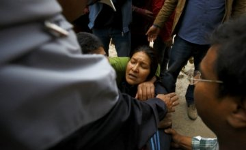 Rescue team member works to dig out the trapped body of a woman from a collapsed house a day after an earthquake in Bhaktapur, Nepal April 26, 2015. Rescuers dug with their bare hands and bodies piled up in Nepal on Sunday after the earthquake devastated the heavily crowded Kathmandu valley, killing at least 1,900, and triggered a deadly avalanche on Mount Everest. REUTERS/Navesh Chitrakar