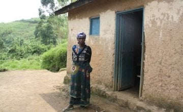 Sarah Nyirabagende stands outside her home in Kazinga Village. Photo taken by Concern Worldwide.
