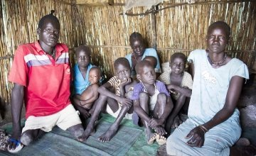 Nyadom Machar Raynem (far right), 48, James Gatchang (far left), 20, and their family sit in their shelter in the displacement camp on the UN base in Bentiu. Photo: Concern Worldwide.