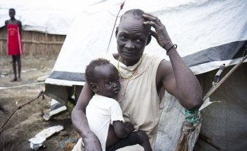 Nyalada Maluit holds her two-year-old son, Lat Machar, in front of their home in the displacement camp on the UN base in Bentiu, South Sudan. Photo: Concern Worldwide.