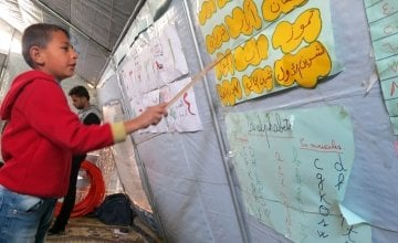 A young Syrian boy, studying both Arabic and Roman alphabets. Photo: Concern Worldwide.