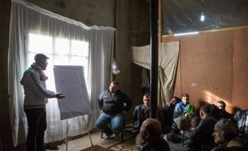 Concern Protection Field Officer Rami Fares, left, gives a session on violence to Syrian refugee men in Tal Abbas in Akkar, northern Lebanon. Photo: Dalia Khamissy / Concern Worldwide.