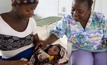 Eighteen year old Doris Kpah cradles her newborn baby under the proud gaze of Alice M Narmah, Nurse Midwife at John Logan Town Community Care Center. Photo taken by Kieran McConville/Concern Worldwide.