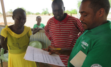 Dr Francis Nkakojoo, Concern's Health and Nutrition Programme Manager with Mary Nyandit and Mol Garang providing advice on completing reports on screenings for malnutrition at Mayen Ulem Primary Health Care Centre