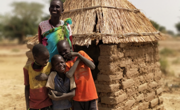 One of our beneficiaries, Theresa Abuk Dut, with her three sons outside their newly-constructed household latrine. Photo: Malek Deng Aguot