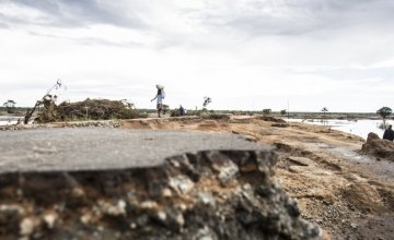 People walk on the remains of a road in Malei, one of the most flood-ravaged areas of Zambezia. Photo: Crystal Wells / Concern Worldwide.