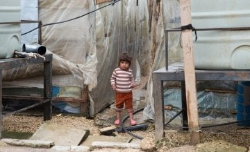 A Syrian refugee girl stands next to the water tanks at an informal tented settlement in Akkar, north ofLebanon. Photo taken by Dalia Khamissy/Concern Worldwide.