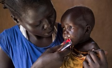 Aweng Ayii (25) and her 10-month-old daughter, Adut Ayii Garang,at their home in Nyamel, Northern Bahr el Ghazal in South Sudan. Aweng is feeding her ready-to-eat therapeutic food (RUTF), supplied as part of the programme. Photo: Kieran McConville/Concern Worldwide.