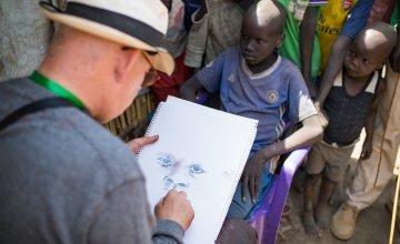 Irish artist Brian Maguire sketches a young boy in the POC of Bentiu, South Sudan. Photo: Steve De Neef / Concern Worldwide.