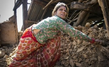 In a Nepalese village, Chandra stands amongst the wreckage of her home. Photo taken by Crystal Wells/Concern Worldwide.