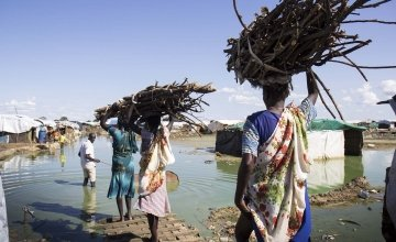 Women carry firewood back to their homes through contaminated flood water in the displacement camp on the UN base in Bentiu. Photo: Concern Worldwide.