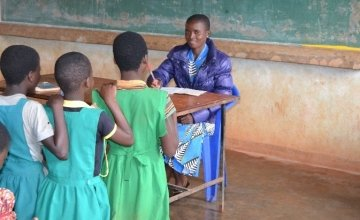 Mercy Mwadula marking her learners exercise in class as they await their turns to be marked. Photo: Concern Worldwide.