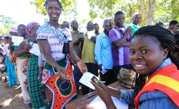 Triphonia Jonathan, (30) receiving a cash transfer from Nuciana Njolomola, 45 an agent used by Concern Worldwide, Chazuka Village, Mchinji, Malawi Photo by Jennifer Nolan.