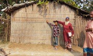 Community members in Vati Kapasia, Kapasia Union, Sundarganj, Bangladesh show the level of the flood water from the 2019 monsoon on their home. Photo: Finola Mohan / Concern Worldwide.