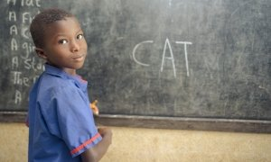 A student in class 1 at Benevolent Islamic Primary School in Makinth community writes on the black board