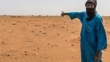 Mahamadou Islam Garmaz, Chief of Garmazaye village, points to the arid landscape