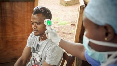 A visitor (Wilson Amadu) to Allen Town PHU has his temperature taken before entering the PHU. All patients and visitors are screened for symptoms of Ebola before entering the PHU. Photographer: Michael Duff.