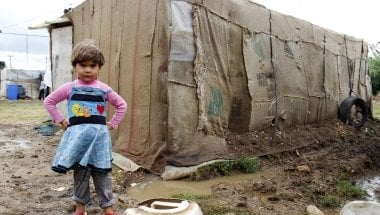 A refugee child stands in front of her home in an informal tented settlement in Akkar district.