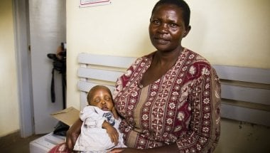 Esther, 40, cradles her child, Euticus, one year three months, at Baraka Health Centre in the heart of Mathare slum. Euticus, who has severe malnutrition as well as tuberculosis, is receiving treatment at the health centre, which is one of 107 clinics supported by Concern Worldwide across eight slum communities in Nairobi and Kisumu. Photo taken by Crystal Wells / Concern Worldwide