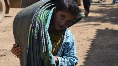 A young boy receives blankets at a Concern distribution at the refugee camp in Turkey. Photo taken by Fionnagh Nally.