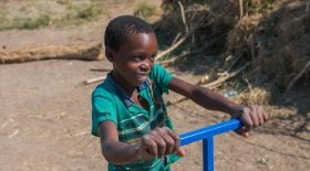 Liven, 13, uses the treadle water pump that Concern provided to his mother