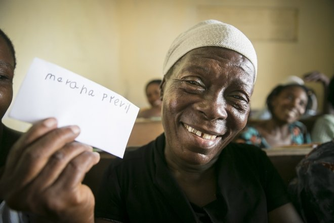 Merana Previl (63) with her written name. Photo: Kieran McConville / Concern Worldwide.