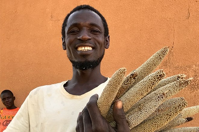37-year-old Mika Abdu proudly displays some of his short-season millet crop, grown from seeds supplied by Concern. Photo: Darren Vaughan/ Concern Worldwide.