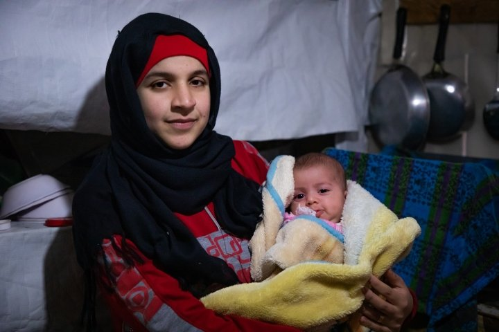 Wafdeh* (20) with her youngest daughter Rajaa* (2 months) with their thermal blanket in their makeshift kitchen. Photo: Gavin Douglas / Concern Worldwide.