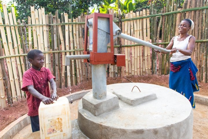 Naomi collects water with her son Lawrence. The village pump was installed through a Concern programme in Liberia. Photo: Gavin Douglas/ Concern Worldwide.