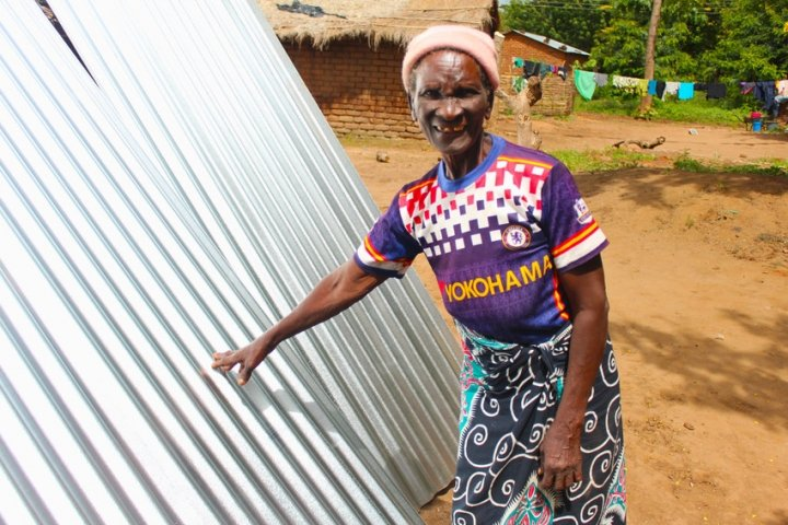 Dorcia (71) with her brand-new waterproof roof sheets. Photo: Jason Kennedy / Concern Worldwide