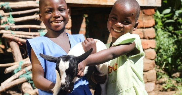 Sisters Esther and Jane Nyirenda hold one of their goats. Photo: Jennifer Nolan / Concern Worldwide.