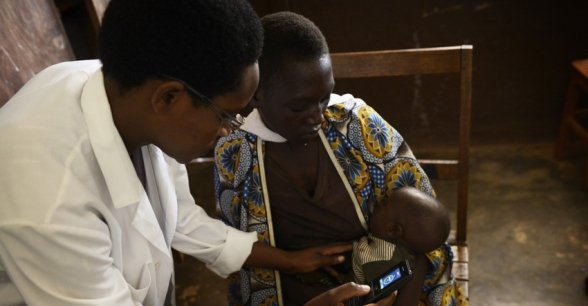 Nurse Orene Nahimana measures three-month-old Roger Bimenyimana's rate of breathing to diagnose if he has pneumonia. Photo: Concern Worldwide.
