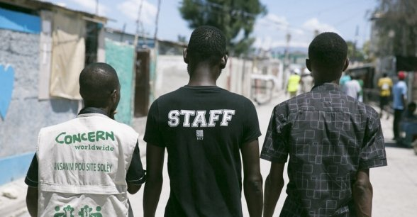 "Pascal Louissant, Concern Haiti, walks through Cité Soleil with members of a local ""Foundation"". Photo: Concern Worldwide."