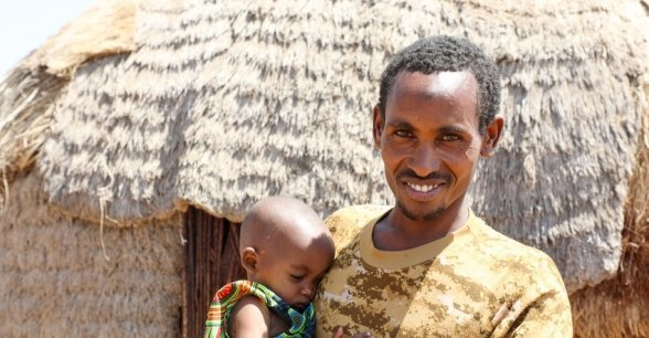 Ishmael Ali outside the tukal he shares with his wife Khayro and their four children. Photo: Jennifer Nolan / Concern Worldwide.