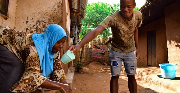 Marriam Jamali received soap as part of of hygiene distribution to help prevent the spread of Covid-19 by Concern in Lilongwe. Her son Bruno helps pour water on her hands while she washes them.