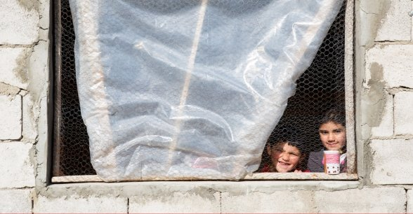 Syrian refugee Afaf, 8, and her younger brother Hani, 4, stand by the window of the kitchen in the collective shelter where they live with their family in Akroum, in Akkar, north Lebanon. Photo: Dalia Khamissy / Concern Worldwide.
