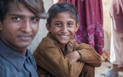 Two young boys sit in a village near Umerkot, Bangladesh. Photo: Black Box Sounds / Concern Worldwide.