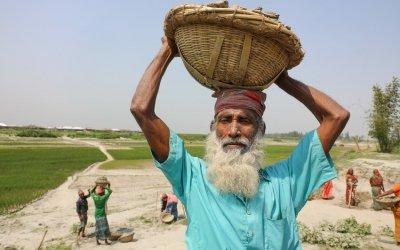 Arman receives cash for work outside Fuljhar primary school. Photo: Jennifer Nolan / Concern Worldwide.