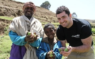 Smiling Apple Farmers, Father and son, Ebrie and Mohammed Ali Demsie with Rob Kearney showing their crops in Dessie Zuria, Ethiopia. Photo: Jennifer Nolan / Concern Worldwide