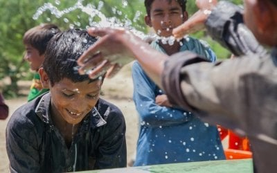Somro and Kishore from Satla Bheel village playing with water at the newly installed plant system. Photo: Black Box Sounds / Concern Worldwide.