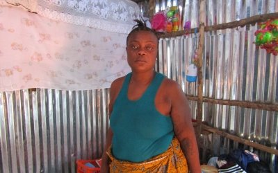 Woman stands in her new home in Kroo Bay