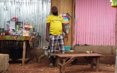 Man stands outside his new home in Kroo Bay.